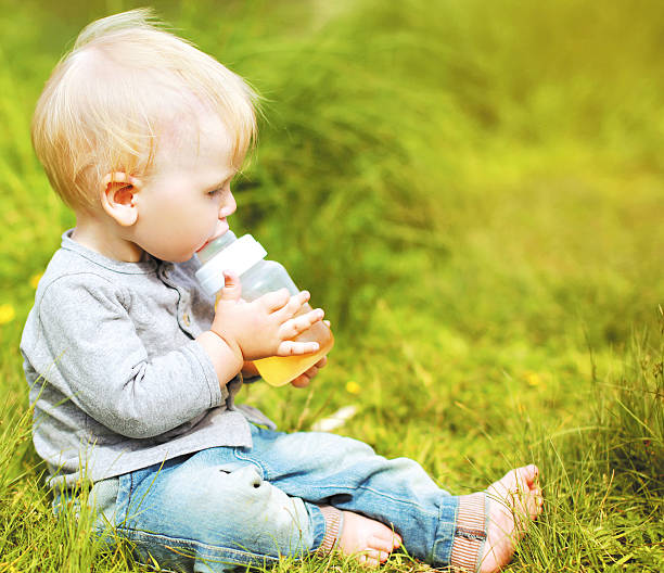 Little baby drinks from a bottle stock photo