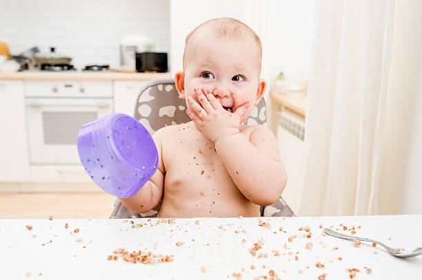 kleine baby essen in der küche. happy unordentlich vogelfamilie - küche lila stock-fotos und bilder