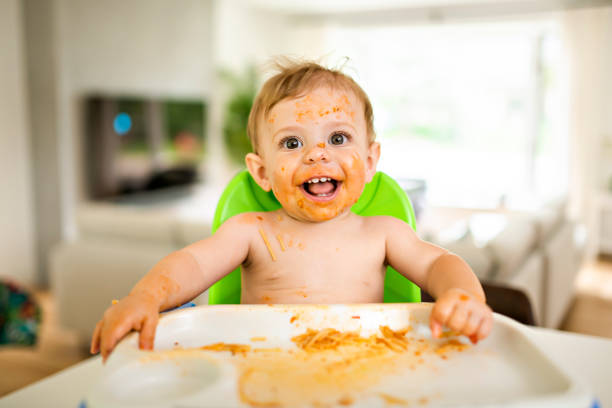A Little baby eating her dinner and making a mess stock photo