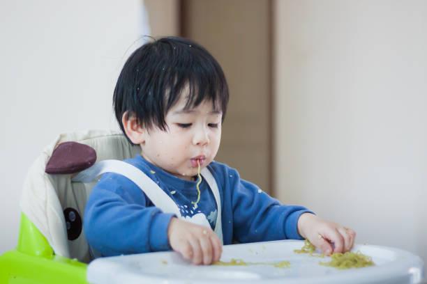 ein kleines baby essen ihr abendessen und ein chaos - kinderstuhl und tisch stock-fotos und bilder