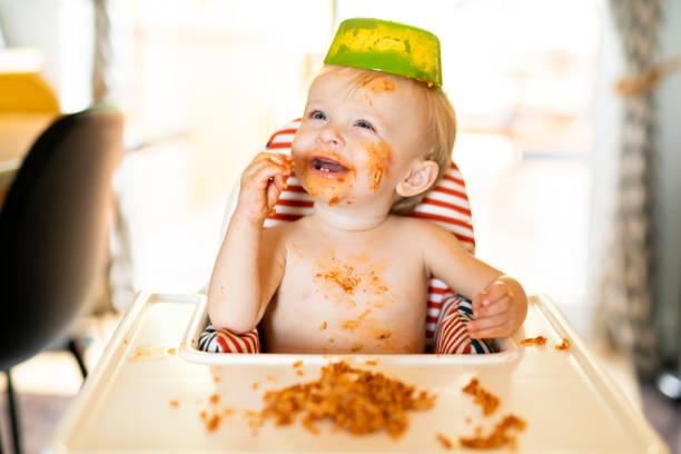 little baby eating spaghetti dinner and making a mess - desarrumação imagens e fotografias de stock