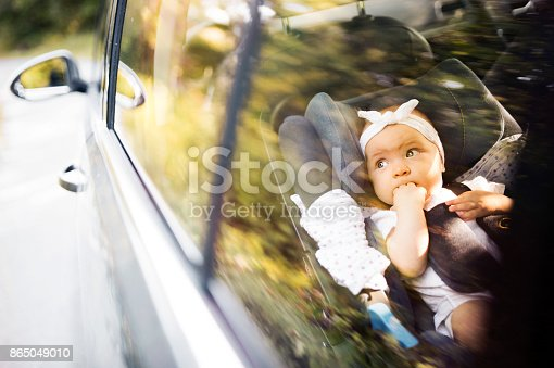 istock Little baby fastened with security belt in safety car seat. 865049010