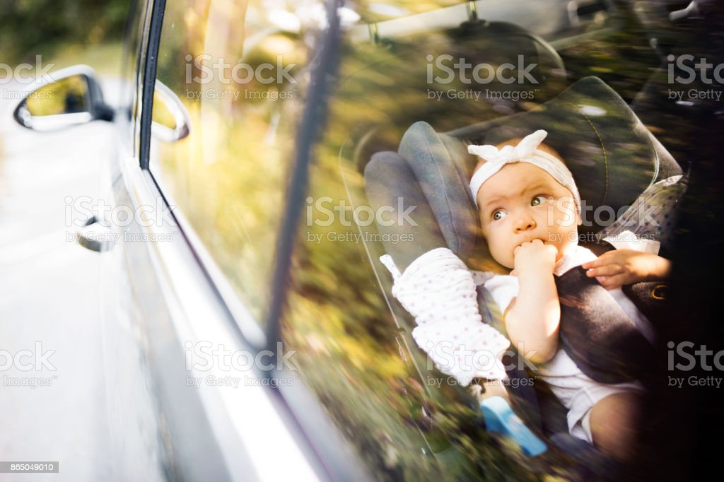 Little baby fastened with security belt in safety car seat. stock photo