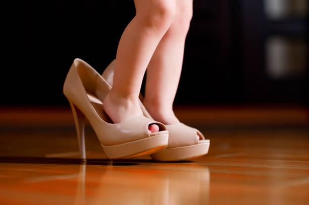 pies de bebé en los zapatos de tacón alto de la mamá - foto de stock