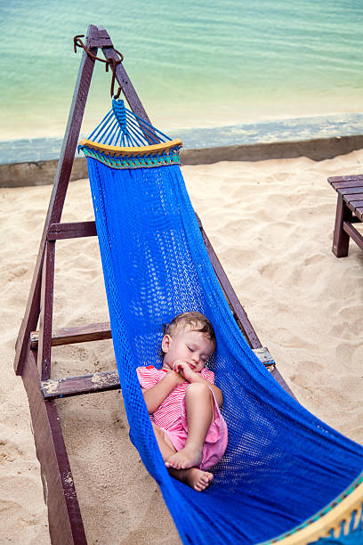 Little baby girl asleep on hammock at the sea beach stock photo