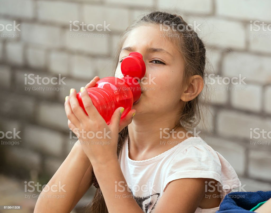 Little baby girl drinking water of red plastic flask stock photo