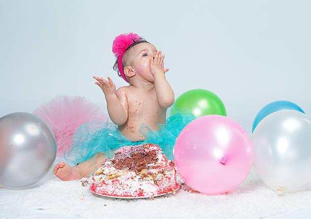 wenig baby mädchen essen geburtstagstorte während der kuchen smash-party - windel partys stock-fotos und bilder