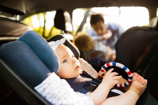 Kleines Mädchen mit Sicherheitsgurt im Auto-Kindersitz befestigt. – Foto