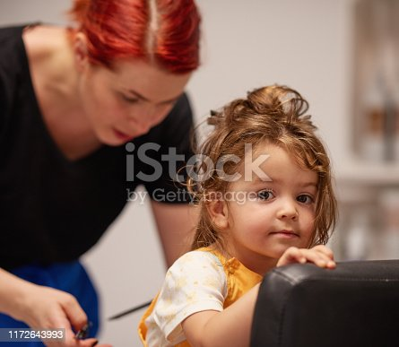 Little baby girl getting a haircut at the hair salon, looking at the camera