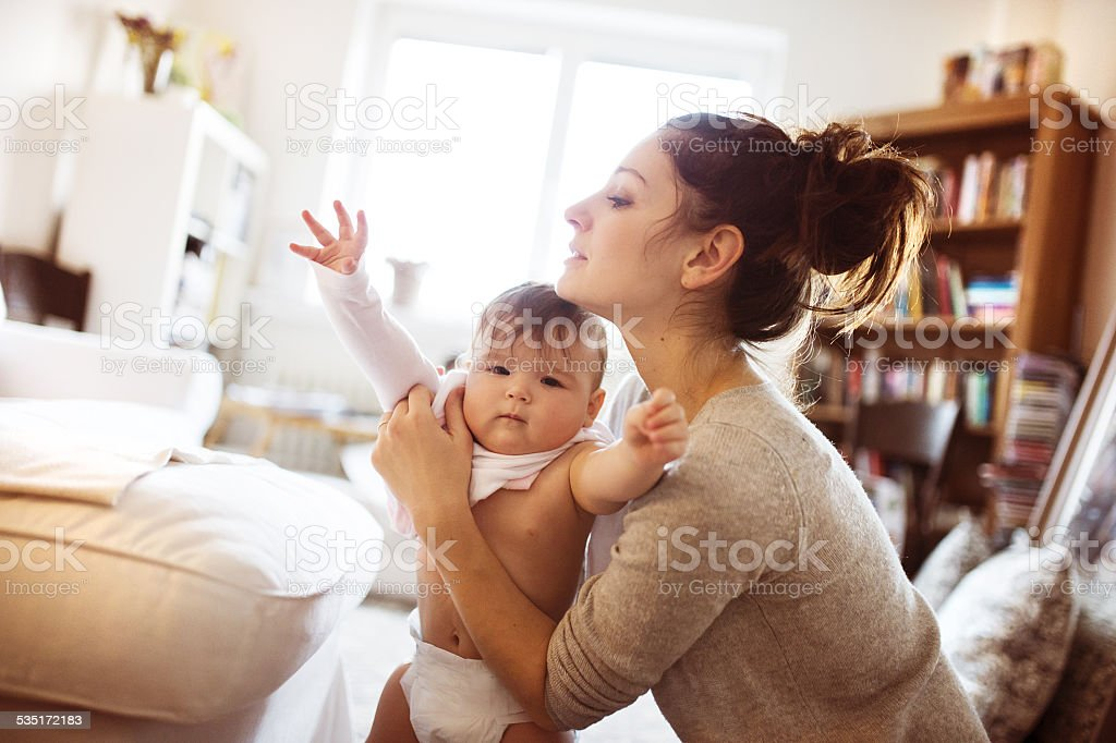 Little baby girl getting dressed by her mother stock photo