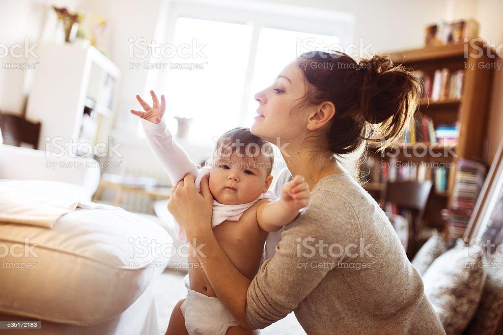 Pequeno Bebê Menina vestir-se por sua mãe - foto de acervo