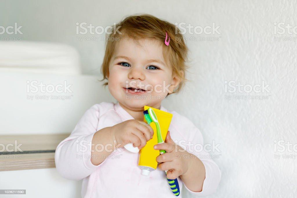 Kleines Mädchen hält Zahnbürste und Bürsten ersten Zähne. Kleinkind lernen, saubere Milchzahn. – Foto