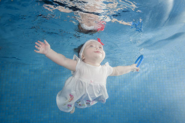 Little baby girl in white dress dives underwater in a swimming pool stock photo