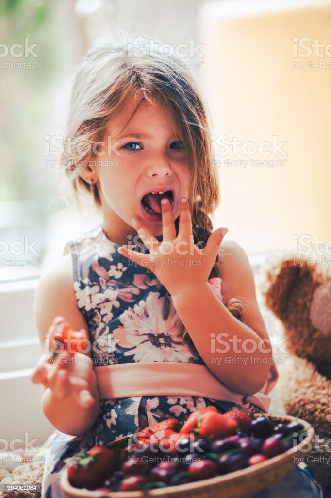 Little  baby girl is eating strawberry at her room - Royalty-free Baby - Human Age Stock Photo