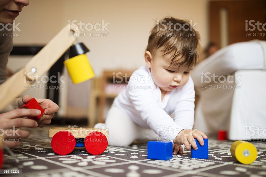 Little baby girl playing with her mother stock photo