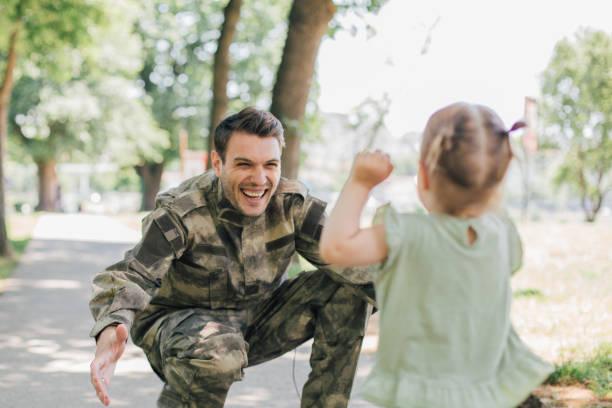 little baby girl running towards soldier - veterans day стоковые фото и изображения