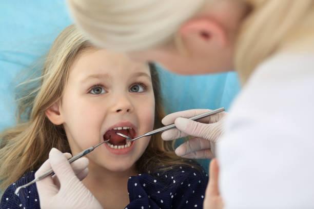 Kleines Mädchen, das auf Zahnstuhl mit offenem Mund sitzt und Angst beim Mundcheck beim Arzt hat. Zahnarztpraxis. Medizinkonzept – Foto