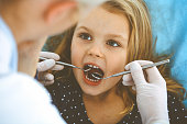 Little baby girl sitting at dental chair with open mouth during oral check up while doctor. Visiting dentist office. Medicine concept. Toned photo.