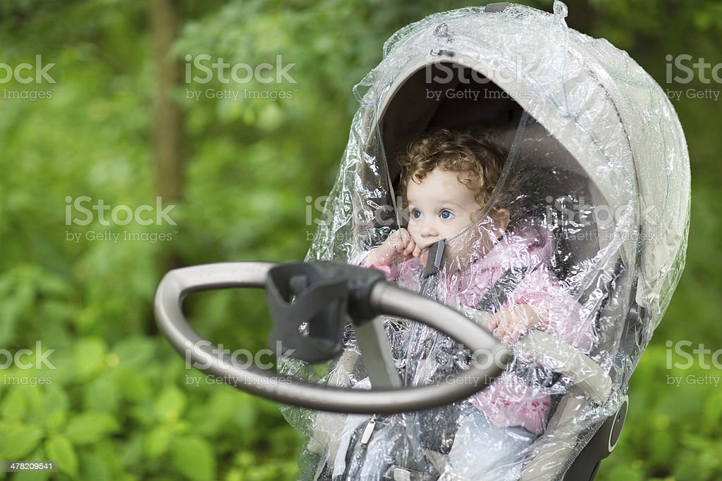 Little baby girl sitting in stroller under rain cover royalty-free stock photo