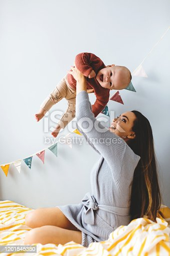 538360916 istock photo A little baby girl smiles and plays on the bed with her mom 1201545380