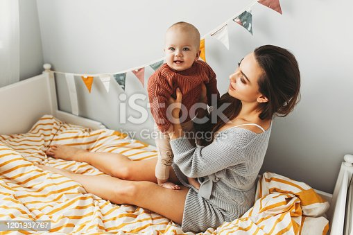 538360916 istock photo A little baby girl smiles and plays on the bed with her mom 1201937767