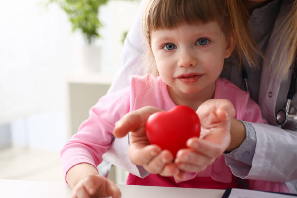 Little baby girl visiting doctor holding in hands red toy heart stock photo