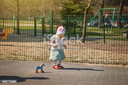 istock Little baby girl walking with a wooden horse on a rope. 946710460