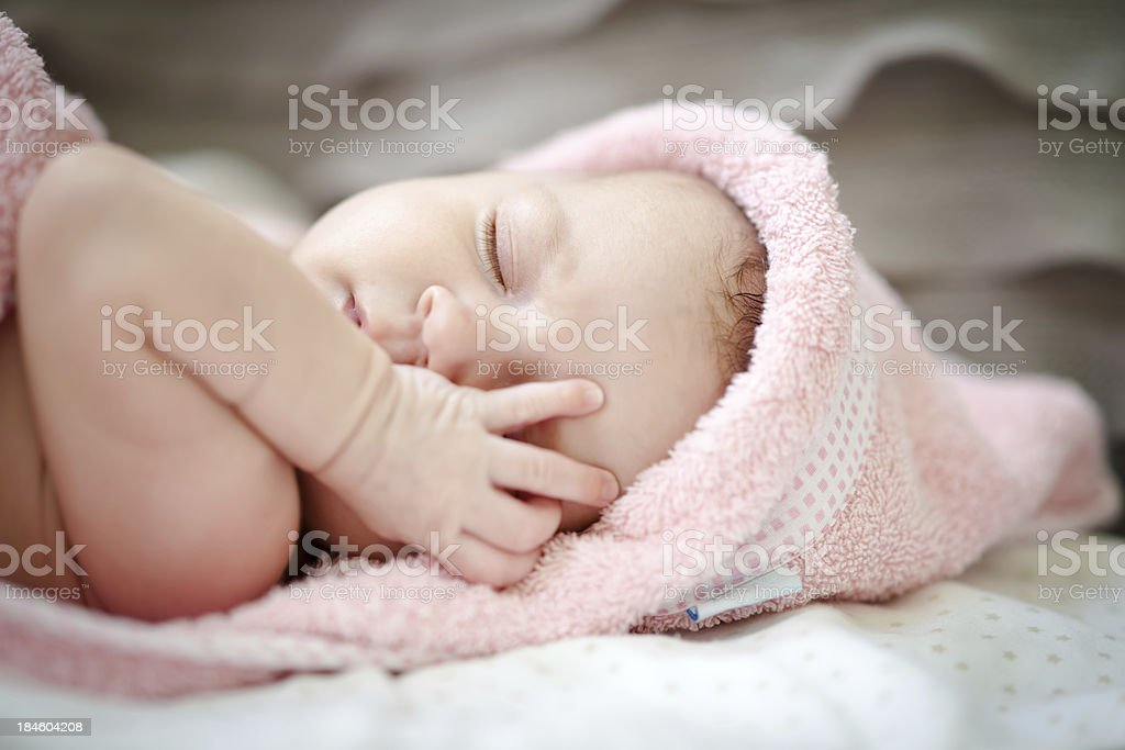 Little baby girl wants to sleep Little cute baby girl in pink towel gently holds her hand near eye 0-11 Months Stock Photo