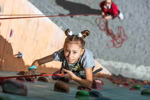 Little baby girl with funny hear style doing rock climbing – Foto