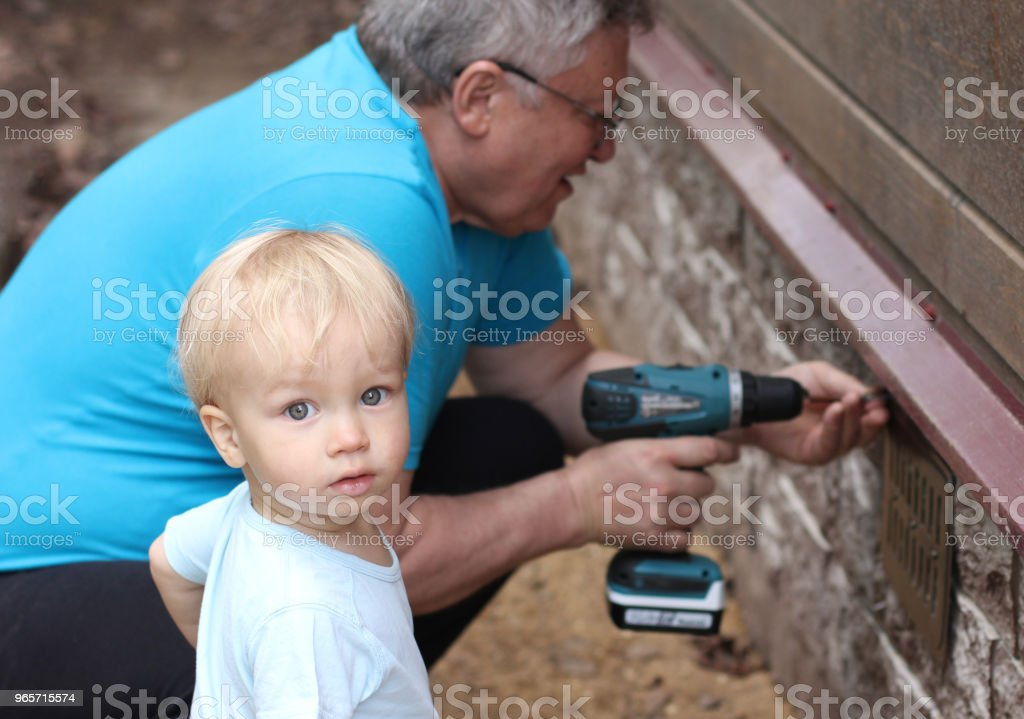 Little baby grandson and his grandfather works with screwdriver (fastens the ventilation grille). The succession of generations. Focus on boy. - Royalty-free Adult Stock Photo