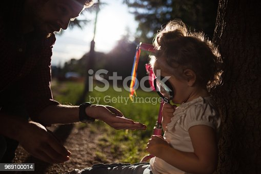 istock Little baby holding magnifying glass in nature 969100014