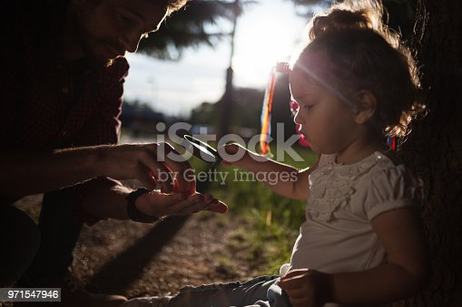 istock Little baby holding magnifying glass in nature 971547946