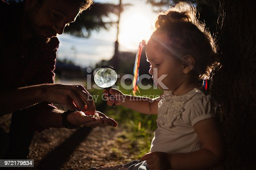 istock Little baby holding magnifying glass in nature 972179834