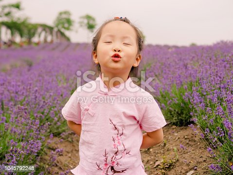 Little baby in a lavender field making faces with eyes closed and pout, beautiful young girl with lovely braid.