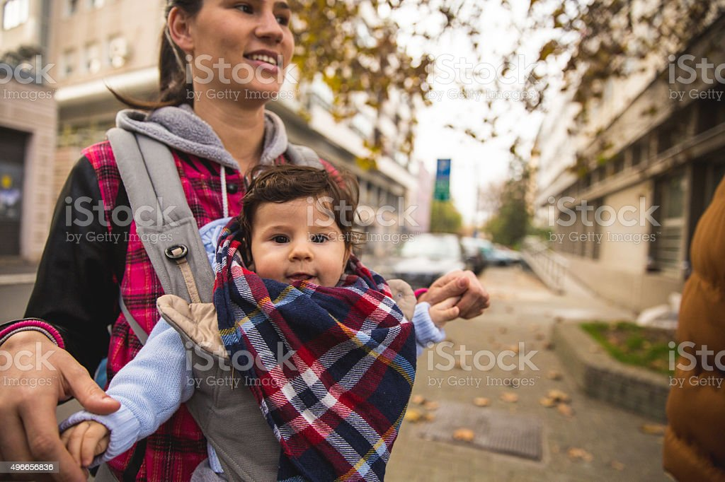 Little baby in baby carrier in city walk stock photo