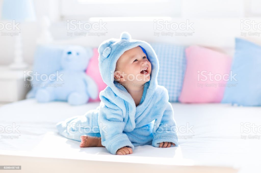 Little baby in bathrobe or towel after bath stock photo