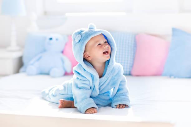 little baby in bathrobe or towel after bath - badewannenkissen stock-fotos und bilder