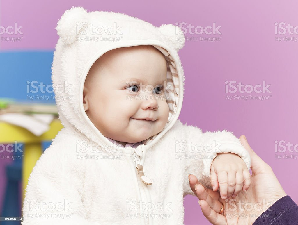 little baby in bear costume smiles and hold mothers hand stock photo