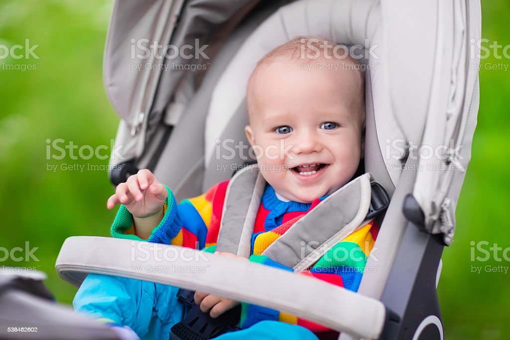 Baby boy in warm colorful knitted jacket sitting in modern stroller...