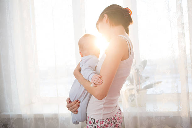 Little baby in the arms of her mother living room. stock photo