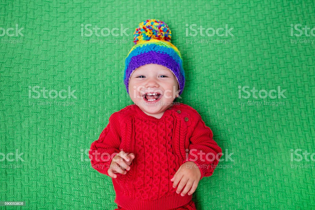 Little baby in warm knitted hat on a green blanke stock photo