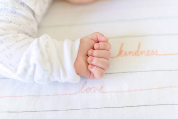 Little baby infant newborn make a fist next to the words love and kindness stock photo