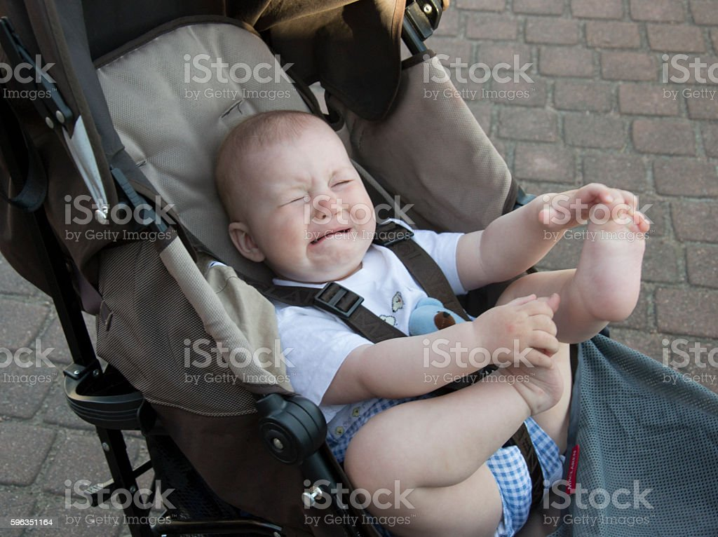 Little baby is crying in baby carriage stock photo