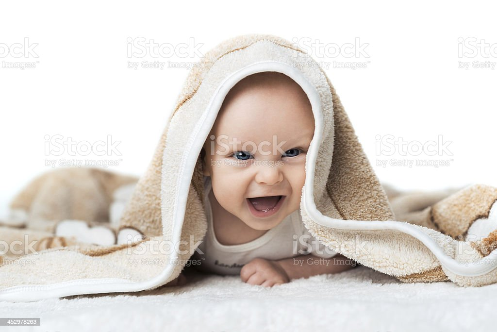 Little baby is laughing under the  carpet royalty-free stock photo