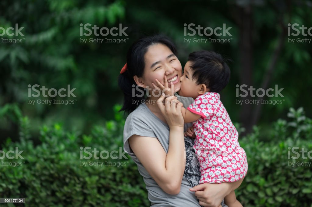Little baby kissing her mother stock photo
