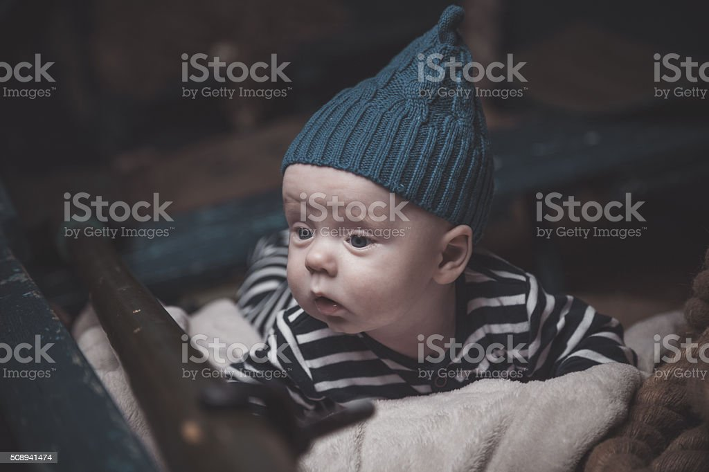 Little baby laying in a boat dressed as a sailor stock photo