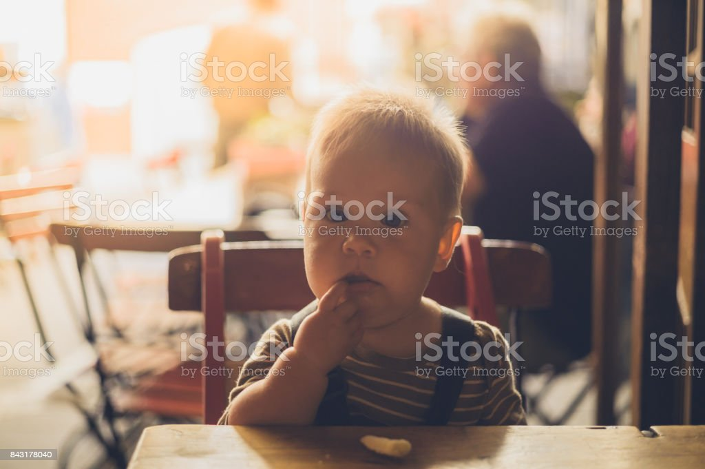 Little baby learning to eat at the table stock photo