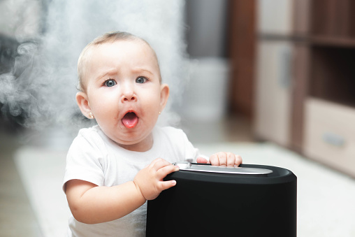istock Little baby looks at the humidifier. Moisture in the house concept 1146730927