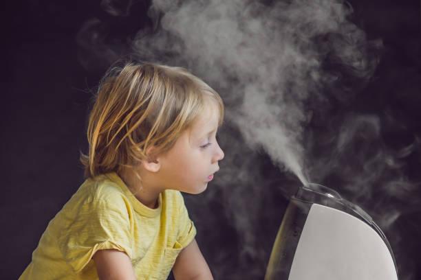 小さな赤ちゃんを見て加湿器 - 加湿器 ストックフォトと画像
