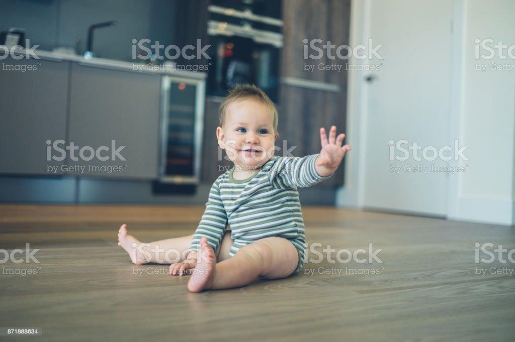 Little baby on kitchen floor waving stock photo